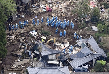 Police officers conduct a search operation at the site of a landslide caused by an earthquake in Minamiaso village, Kumamoto prefecture, Japan, April 16, 2016.
