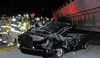 Rescue workers stand before a destroyed car after the collapse of a bridge in an earthquake, April 16, 2016 in Guayaquil, Ecuador.
