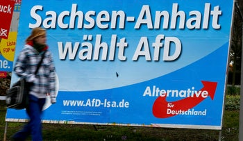 "A pedestrian walks in front of an election poster for the right-wing Alternative for Germany (AFD) party, Magdeburg, Germany, March 11, 2016. The slogan reads ""Saxony-Anhalt vote for AFD."""