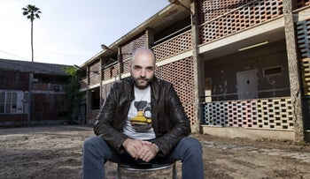"Giora Chamizer on the set of ""Neighborhood."" A world where children can entertain the fantasy of self-definition. Chamizer, with a shaved head and a trim beard and moustache, wears jeans, a T-shirt and a leather jacket and sits on a chair in what appears to be a down-at-heels apartment building or motel, with external halls."