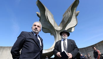 Coordinator of the Jewish communities in Croatia Ognjen Kraus (L) and Croatian rabbi of the Jewish community Luciano Mose Prelevic (R) stand in front of a memorial in the shape of a flower in Jasenovac on April 15, 2016.