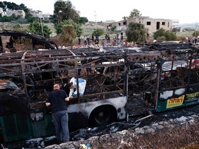 Israeli forensics search in the remains of a burned-out bus after a bomb blast ripped through the vehicle in Jerusalem on April 18, 2016.