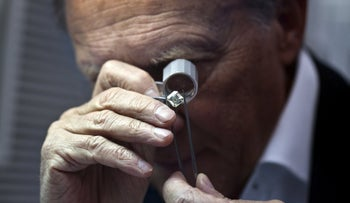 A trader inspects a diamond at the trading floor of Israel's Diamond Exchange (IDE) in Ramat Gan near Tel Aviv, Israel March 19, 2013.
