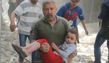 A man carries an injured girl after an airstrike in the rebel held area of old Aleppo, Syria April 22, 2016.