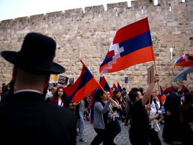 An ultra-Orthodox Jewish man looks at a march in commemoration of the anniversary of the mass killings of Armenians by Ottoman Turks in 1915, Jerusalem, Israel, April 23, 2016.