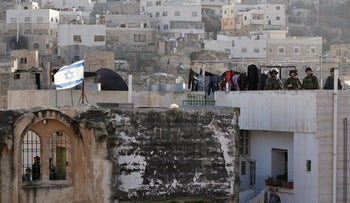 Israeli soldiers and border police stand guard as Israeli settlers take over several houses, which are disputed between Palestinians and Israelis, in the West Bank old city of Hebron, January 21, 2016.