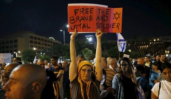 A supporter of Elor Azaria holds a sign during a protest calling for his release in Tel Aviv, April 19, 2016.