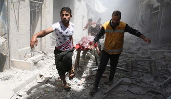 Syrian men carry a body on a stretcher following a reported air strike on the rebel-held neighborhood of Al-Qatarji in the northern Syrian city of Aleppo, on April 29, 2016.