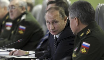 Russian President Vladimir Putin looks at Defense Minister Sergei Shoigu at the National defense control center in Moscow, Russia, March 11, 2016.