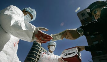 Falun Gong demonstrators dramatize an illegal act of paying for human organs during a protest 19 April 2006 in Washington, DC in conjunction with the visit by Chinese President Hu Jintao to the US.