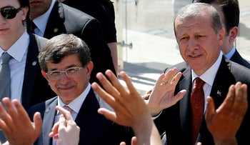 Turkey's then-Prime Minister Tayyip Erdogan (R) and then-Foreign Minister Ahmet Davutoglu greet their supporters as they leave Friday prayers in Ankara, Turkey, August 22, 2014.