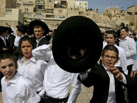 """Ultra-Orthodox Jewish boys protest against members of the activist group """"Women of the Wall"""" during an event for the Passover holiday near the Western Wall in Jerusalem's Old City April 24, 2016."""