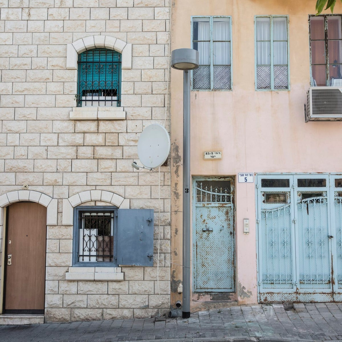 Before and after: Two houses on a street in Jaffa, where house prices have soared in the past decade.
