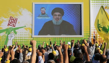 Lebanon's Hezbollah leader Hassan Nasrallah addresses his supporters via a screen during a memorial service to mourn the death of Hezbollah commander Hajj Ismail Zahri, who died due to illness, in Nabatieh, southern Lebanon July 29, 2016.