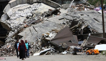 Residents walk past buildings destroyed during security operations and clashes between Turkish security forces and Kurdish militants in the southeastern Hakkari province, Turkey, May 30, 2016.