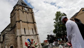 Muslim worshippers hold a minute of silence in front of the memorial at the Saint Etienne church in Saint-Etienne-du-Rouvray, Normandy, France, Friday, July 29, 2016.