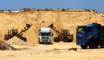 Palestinian diggers dump sand into a truck at the site of Al-Isra 2 housing project in Khan Younis, Gaza Strip, July 20, 2016.