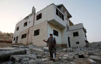 A relative gestures in front of the family house of Palestinian assailant Mohammad Mahamra after it was partially blown up by Israeli troops in a West Bank village near Hebron.