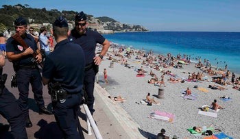 French police patrol on the walkway above a public beach in Nice, France, July 17, 2016.