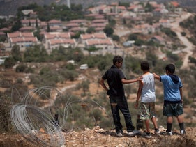 Palestinian children from the West Bank village of Beitillu look out onto the settlement of Nahliel.