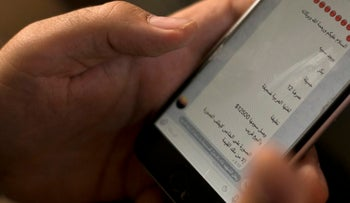 An activist looks at an ISIS marketplace on the encrypted app Telegram, advertising a 12-year-old Yazidi girl as a slave, Iraq, May 22, 2016.