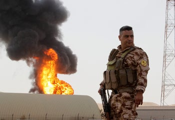 A member of the Kurdish Peshmerga forces stands guard as smoke rises after an attack at Bai Hassan oil station, northwest of Kirkuk, Iraq, July 31, 2016.
