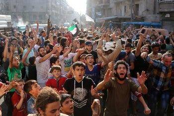 Syrian celebrate in the street after rebels said they have broken a three-week government siege on Syria's second city, Aleppo, Syria, August 6, 2016.