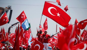 Two men wave Turkish flags at the 'Democracy and Martyrs'Rally' in Istanbul on August 7, 2016.