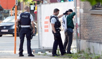 Police officers check the identification of a man near the police headquarters in Charleroi, Belgium on Saturday, Aug. 6, 2016.