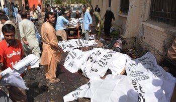 Pakistani volunteers move the body of a lawyer as others cover bodies after a bomb explosion at a government hospital premises in Quetta, August 8, 2016.
