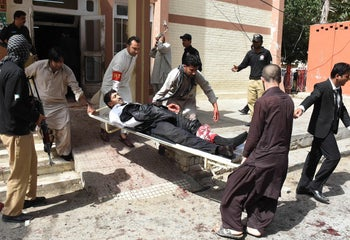 Pakistani volunteers use a stretcher to move an injured lawyer after a bomb explosion at a government hospital premises in Quetta, August 8, 2016.