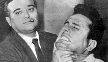 New York City Police Det. Albert Seedman, cigar stub in mouth (left), holding up the face of Tony Dellernia, a suspect in the Borough Park Tobacco robbery, for photographers during a perp walk.