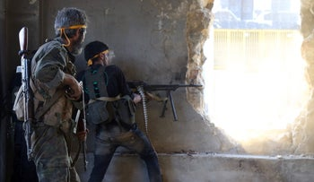 Rebel fighters fire towards positions of regime forces in Ramussa on the southwestern edges of Syria's northern city of Aleppo on August 6, 2016.