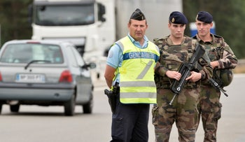 A reservist gendarme and active duty soldiers stand guard a toll on a highway near Le Mans, in Yvre l'Eveque, northwestern France, on August 8, 2016.