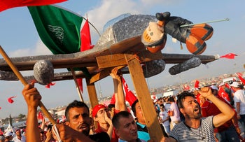 Protesters hold a plane model with an attached toy depicting Muslim cleric Fethullah Gulen during a massive anti-coup rally in Istanbul, Turkey, August 7, 2016.