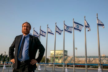 Yehudah Glick standing outside the Knesset, August 3, 2016. In the background is a line of Israeli flags on flagpoles. Glick stands with his hands on his hips.