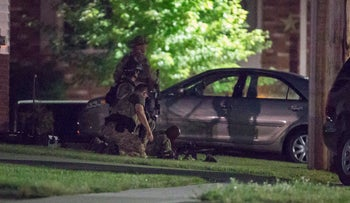 Police keep watch around a house in Strathroy, Ontario, August 10, 2016.
