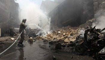 A Civil Defense member tries to put out a fire after an airstrike on al-Jalaa Street in the rebel-held city of Idlib, Syria, August 10, 2016.