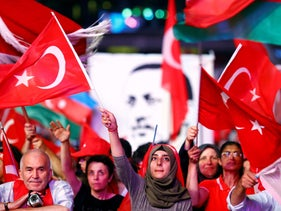 Supporters of Turkish President Recep Tayyip Erdogan wave national flags as they listen to him through a giant screen in Istanbul's Taksim Square, Turkey, August 10, 2016.