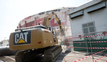 A bulldozer begins demolishing Tel Aviv's historic Cinerama building on August 11, 2016.