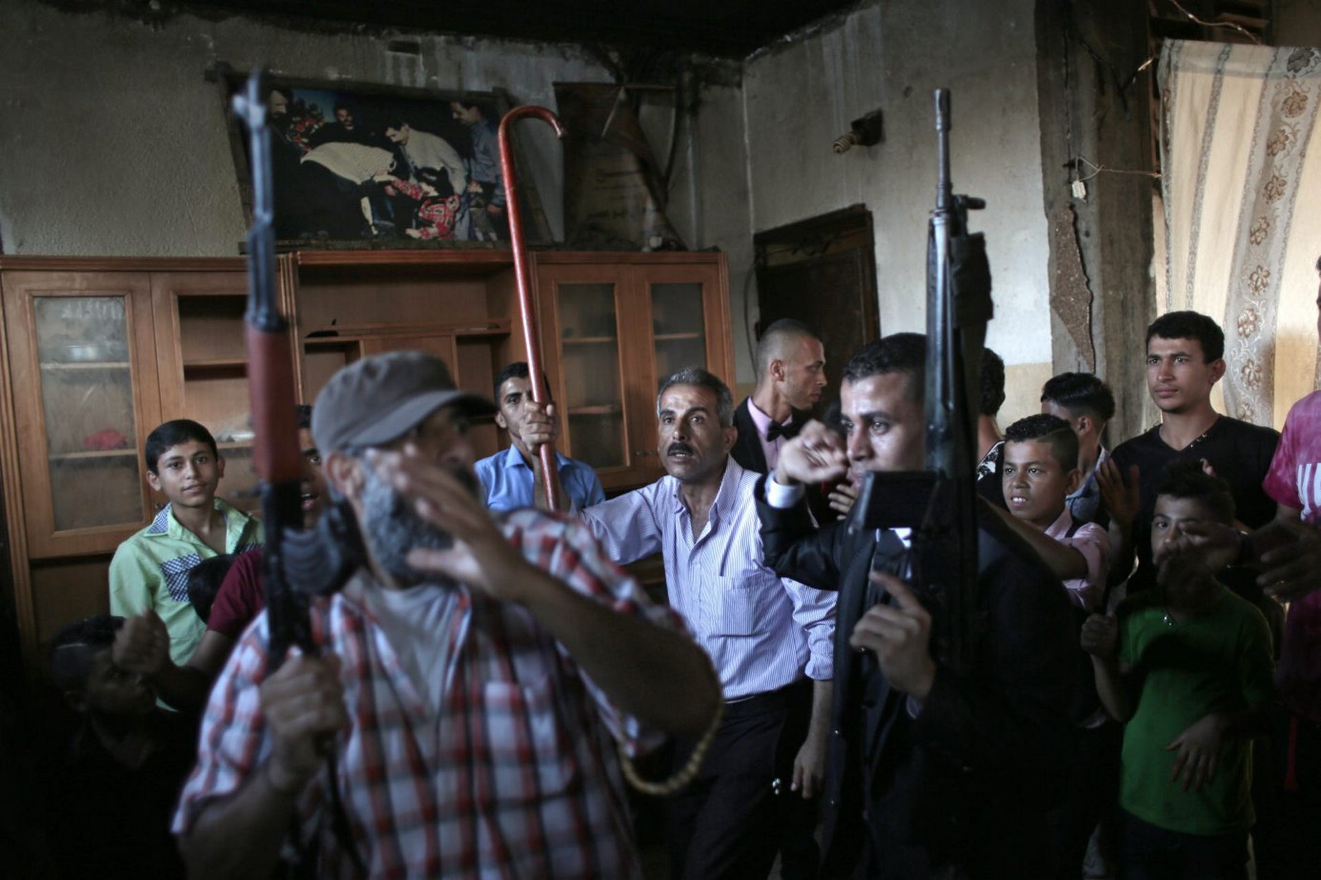 In this Saturday, July 30, 2016 photo, Palestinian groom Saed Abu Aser, center right, dances with relatives while holding guns in the family house during his wedding party, in Gaza City.