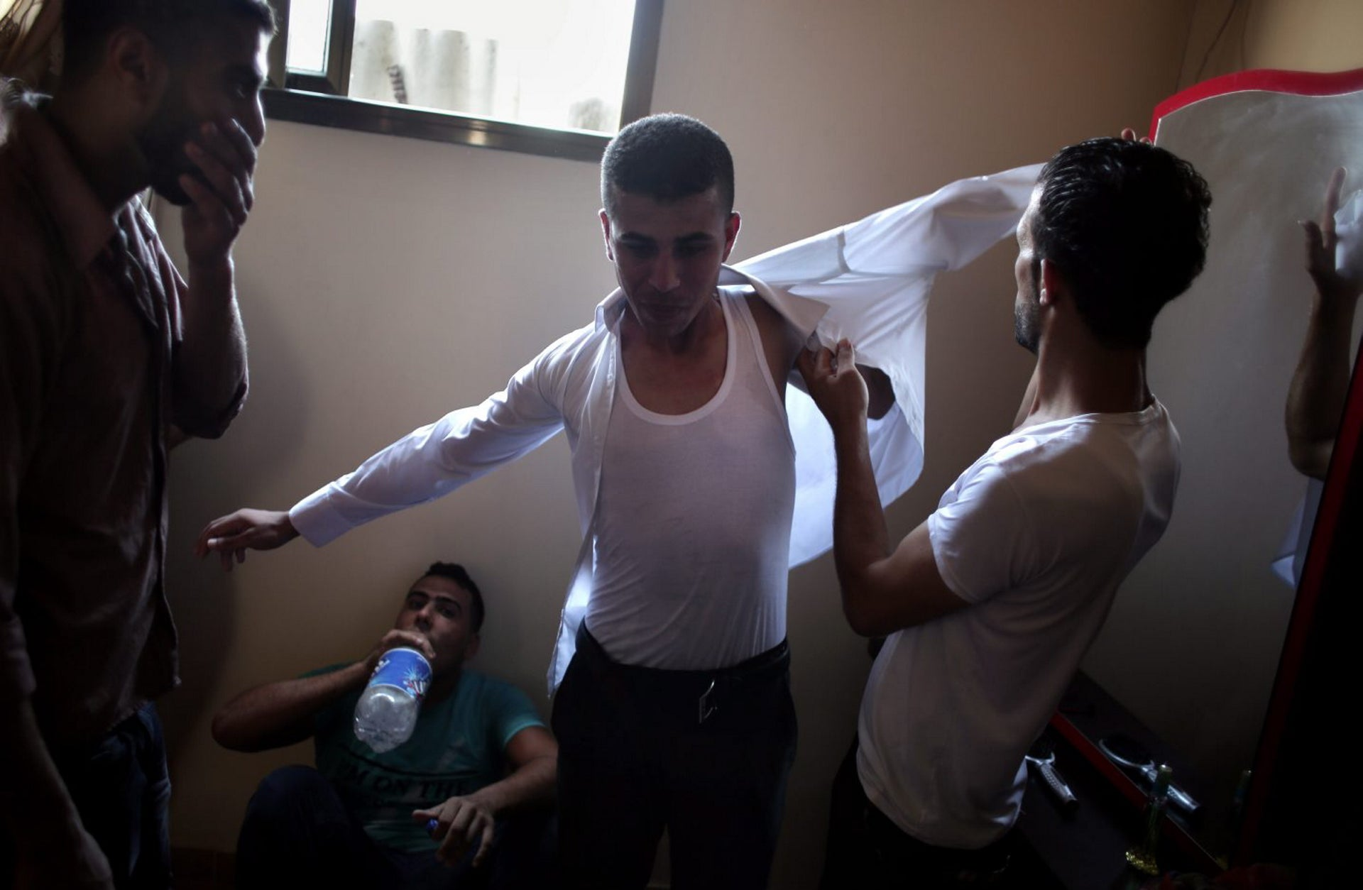 In this Saturday, July 30, 2016 photo, friends of Palestinian groom Saed Abu Aser, help him into his tuxedo in the family house in preparation for his wedding, in Gaza City.