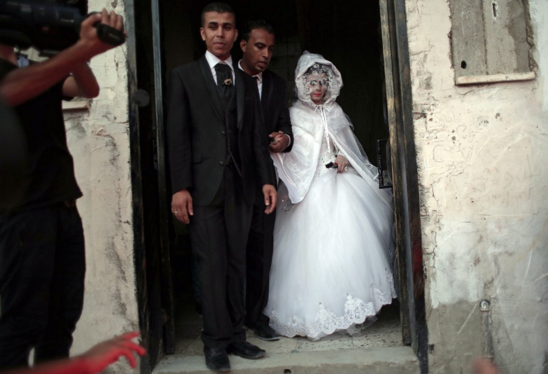 In this Saturday, July 30, 2016 photo, Palestinian groom Saed Abu Aser, 22, walks with his bride, Falasteen, out of her family house to the wedding hall to celebrate their wedding, in Gaza City.