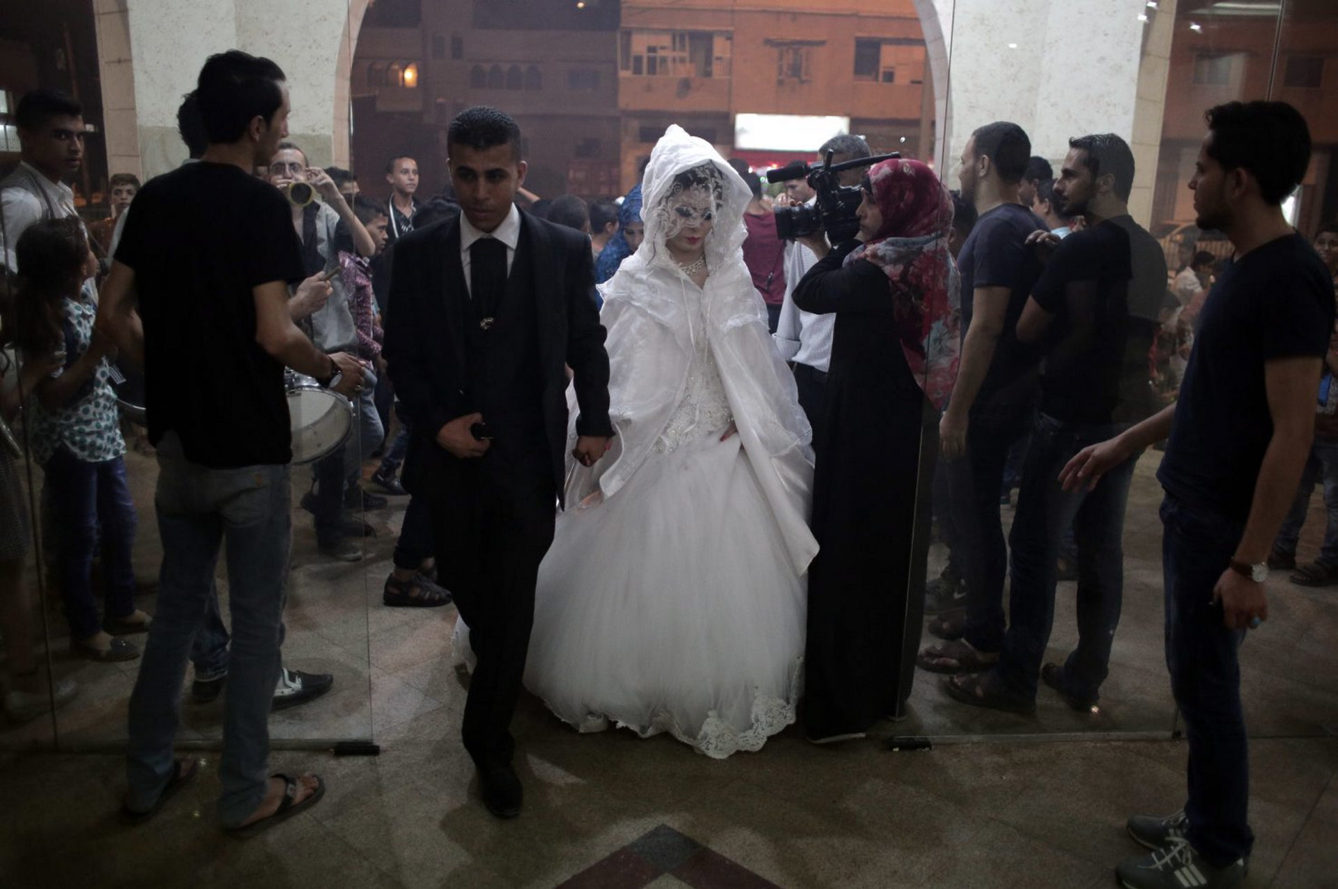 In this Saturday, July 30, 2016 photo, Palestinian groom Saed Abu Aser, and his bride, Falasteen, walk into the wedding hall, in Gaza City.
