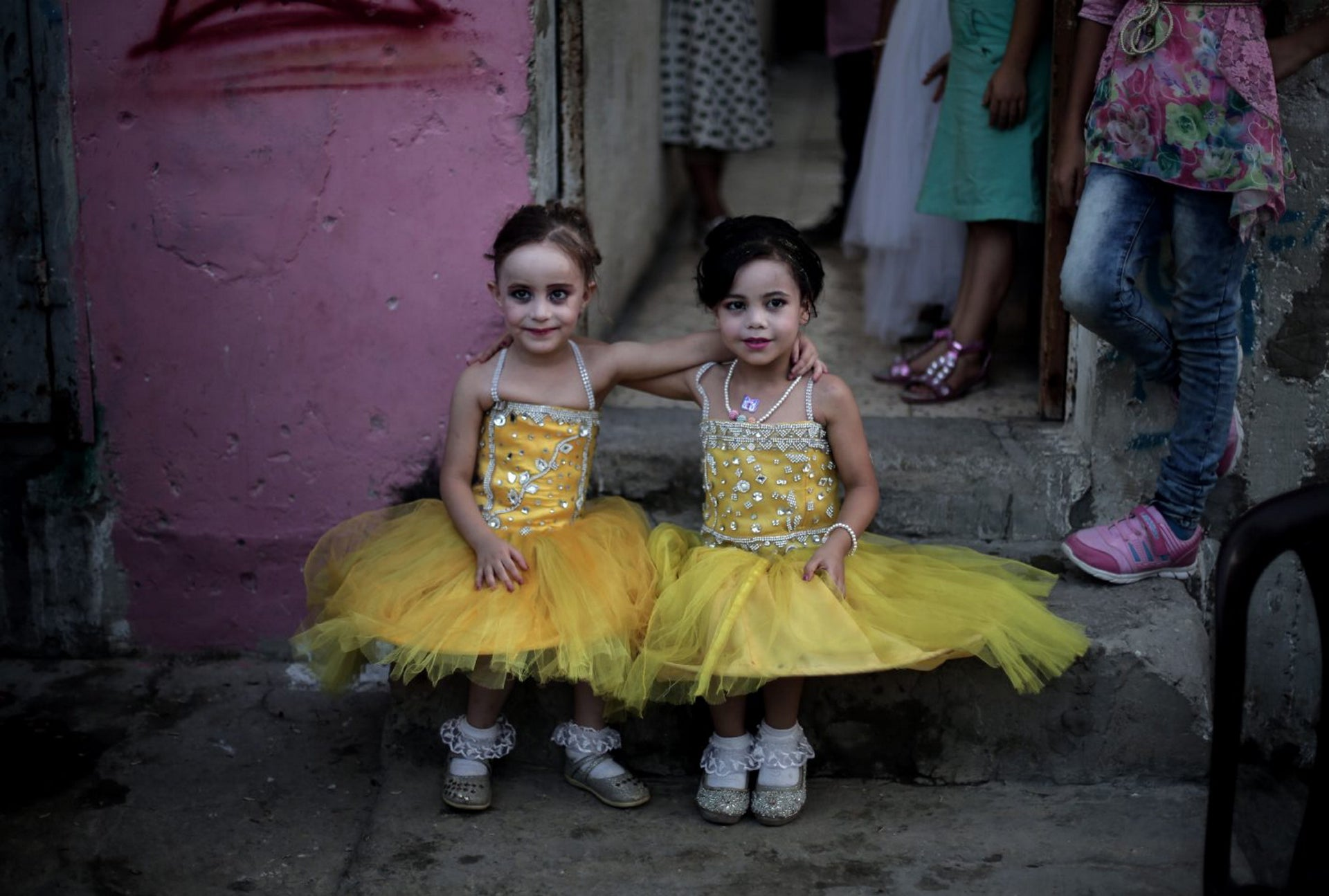 In this Saturday, July 30, 2016 photo, two girls pose for a picture as they sit in front of the family house during the wedding party of Palestinian groom Saed Abu Aser, in Gaza City.