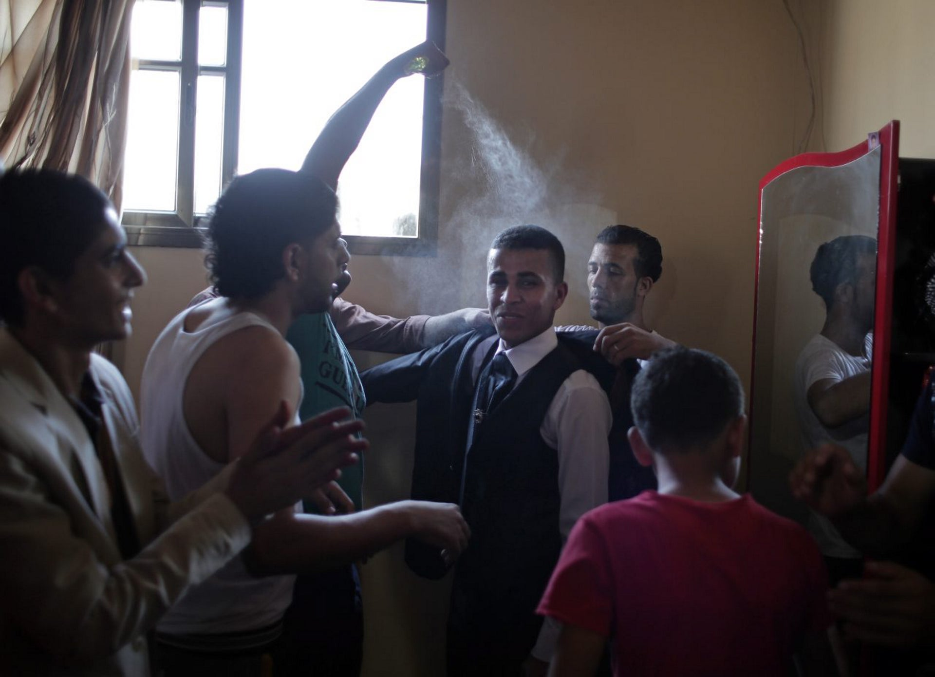 In this Saturday, July 30, 2016 photo, friends of Palestinian groom Saed Abu Aser, spray him with cologne as they help him get dressed for his wedding, at the family house in Gaza City.