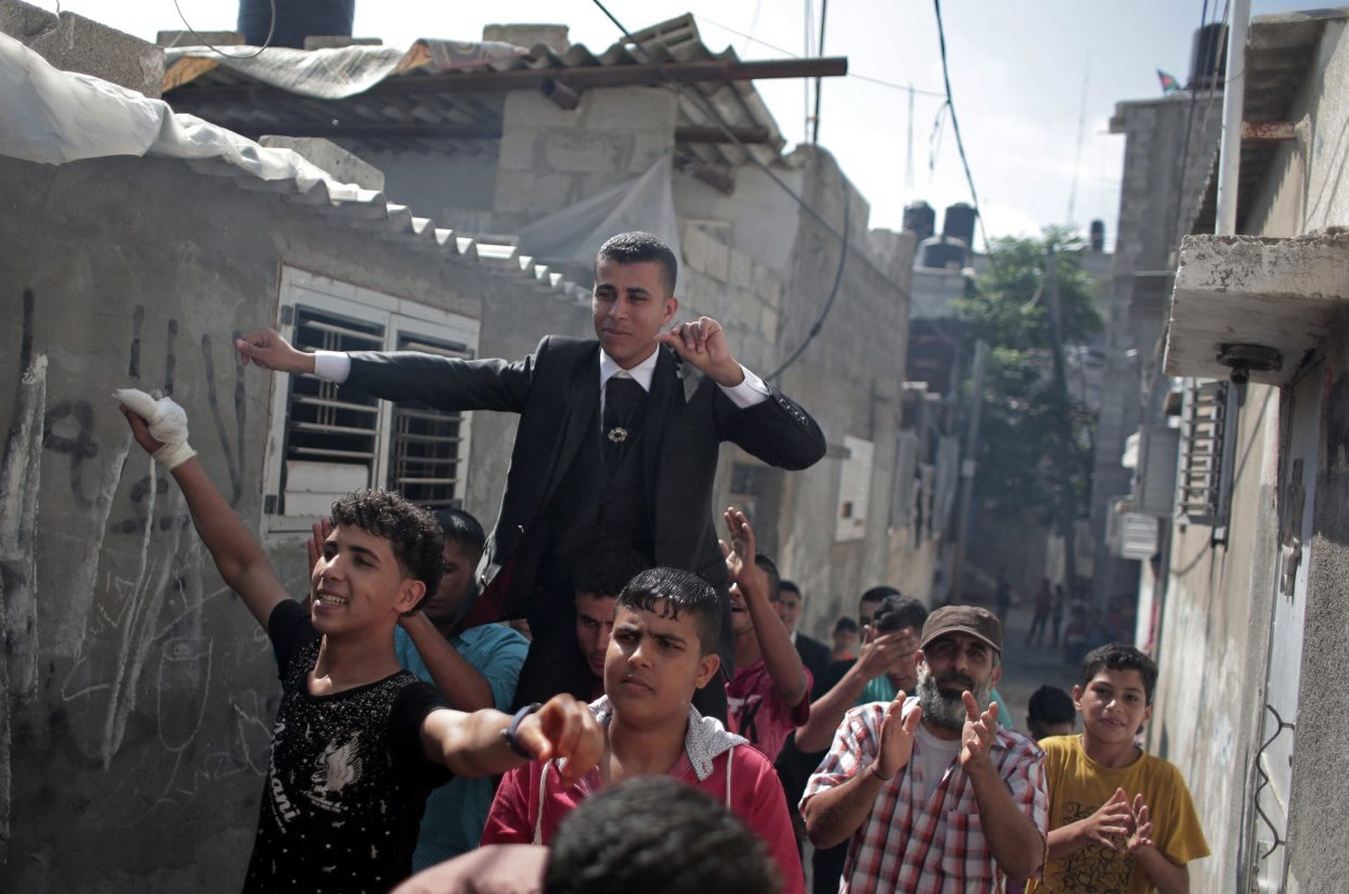 In this Saturday, July 30, 2016 photo, friends and relatives of Palestinian groom Saed Abu Aser dance in the streets around the neighborhood before his wedding in Gaza City.