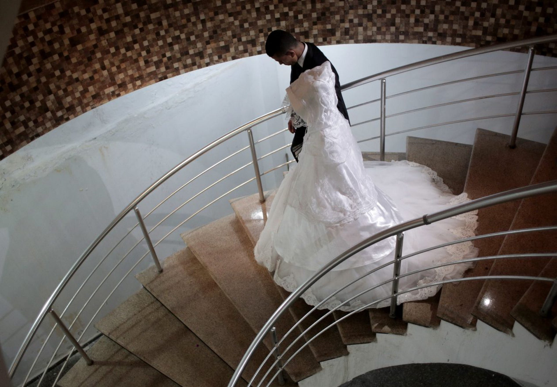 In this Saturday, July 30, 2016 photo, Palestinian groom Saed Abu Aser, and his bride, Falasteen, take the stairs down to the wedding hall, in Gaza City.