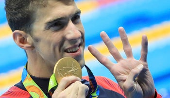 Michael Phelps (USA) of USA gestures to indicate the four gold medals he has won at this Olympic games as he poses with his gold medal.