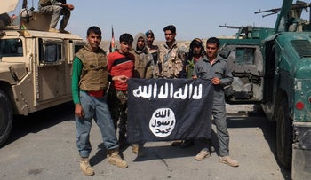Afghan police poses for photograph with an ISIS flag after an operation in the Kot district of Jalalabad province east of Kabul, Afghanistan, August 1, 2016.